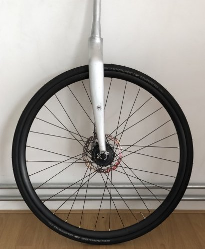 Front wheel fitted to the raw aluminium fork