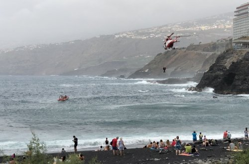 Rescue helicopter lifting persons out of the ocean, notice the volcanic black beach