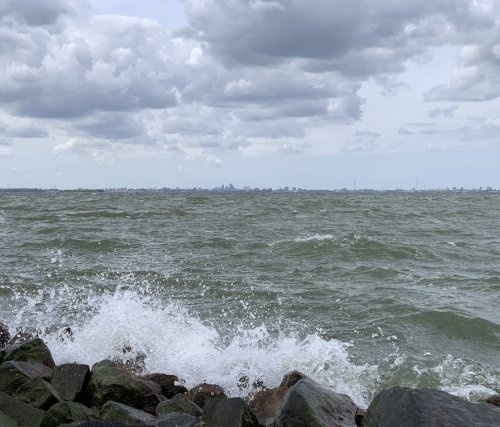 Wind blowing strongly over the water with Amsterdam on the horizon, as seen from Almere